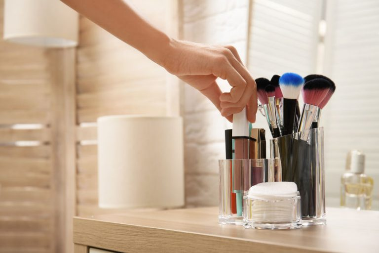 Woman taking lip gloss from organizer for makeup cosmetic products on table