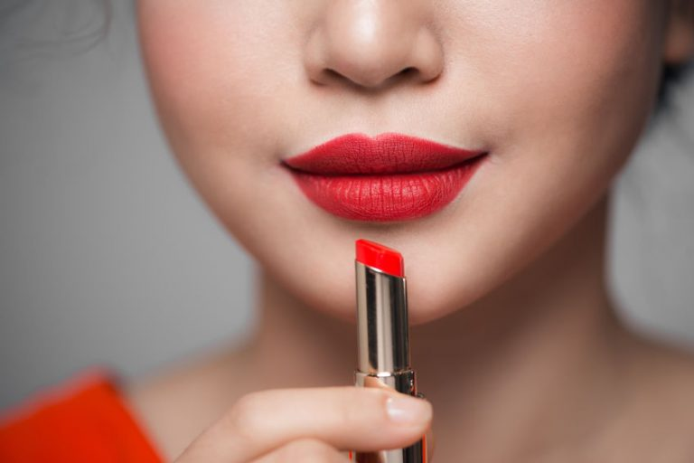 Close up portrait of attractive girl holding red lipstick over grey background