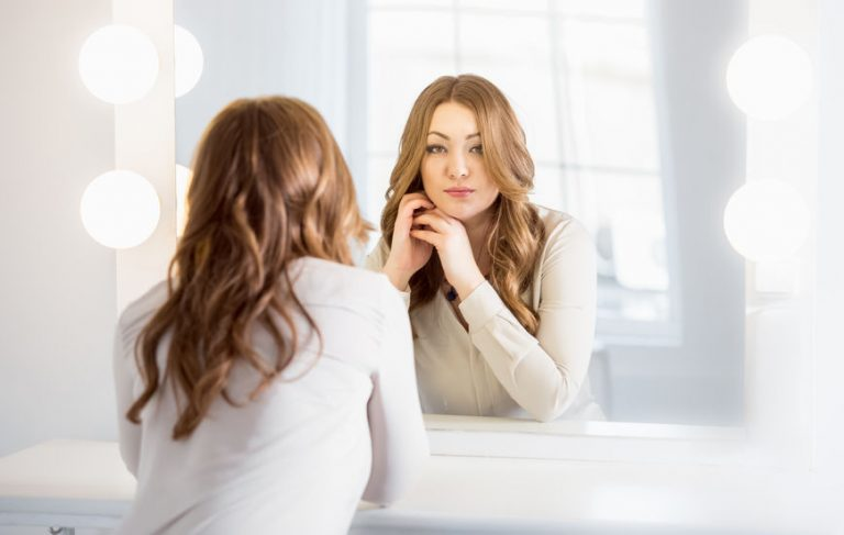 elegant woman with curly hair looking at reflection in mirror